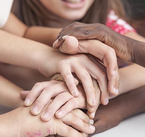 Mãos de diferentes etnias juntam-se.