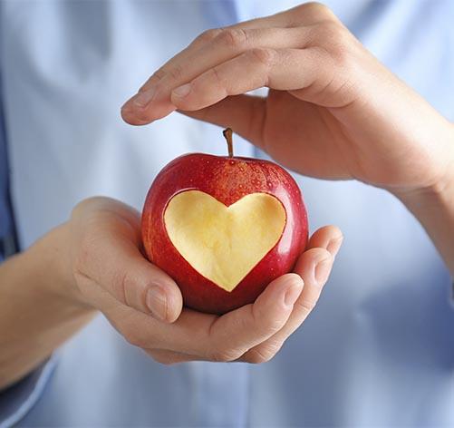 Duas mãos seguram uma maçã em plano próximo.