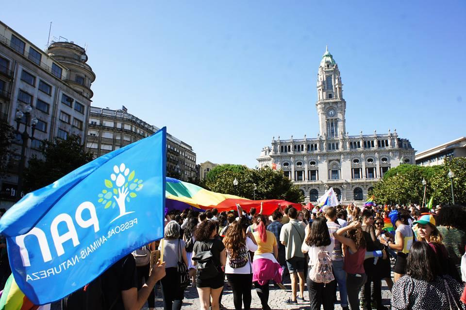 Na imagem podemos ver uma bandeira do PAN e uma grande bandeira arco-íris na Praça dos Aliados, cidade do Porto